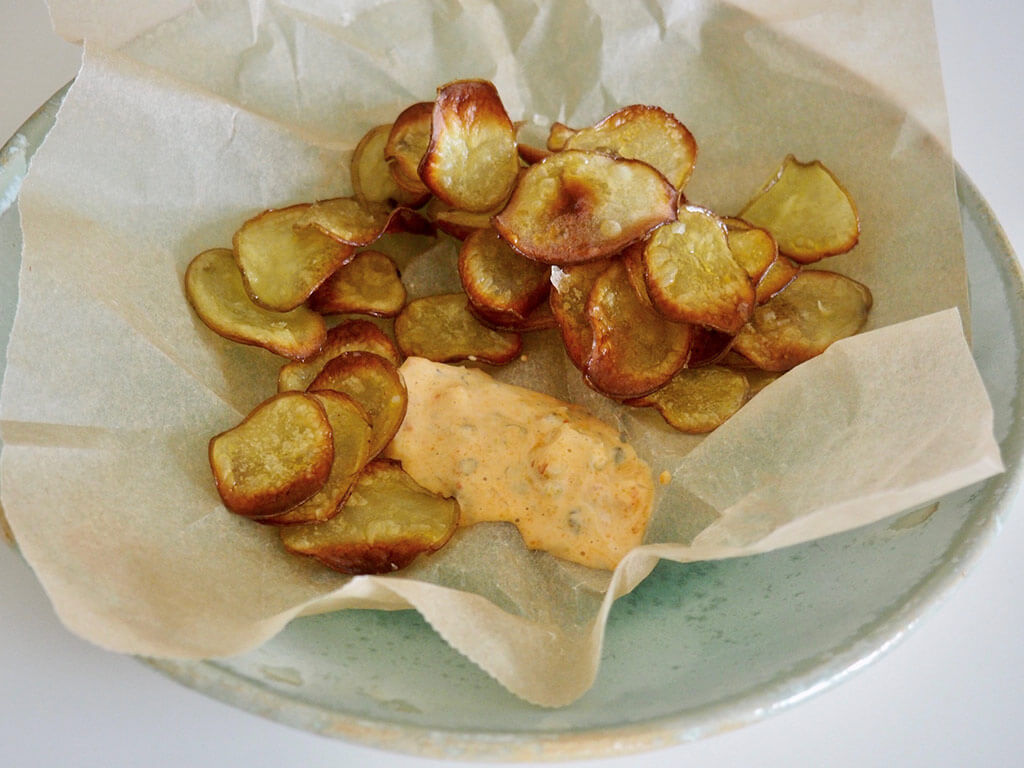 Valmiit perunasipsit leivinpaperilla päällystetyssä kulhossa dipin kera.