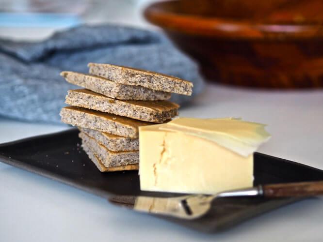 Kaurakakkuset leikattuna palasiksi pinossa juusto vieressä