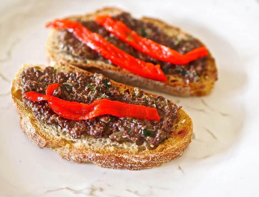 Grillatut leipäviipaleet oliivitahnan ja paprikan kera
