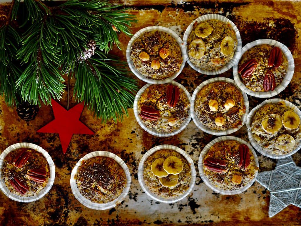 Kuluneella puupöydällä valmiit chiansiemenmuffinit sekä jouluisia koristetähtiä ja kuusenoksa.