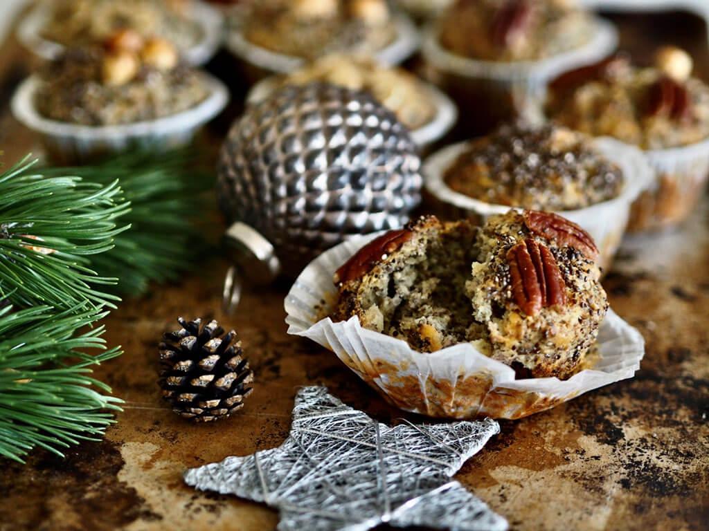 Kypsä raotettu chiansiemenmuffini pöydällä joulukoristeiden sekä kuusenoksan kera.