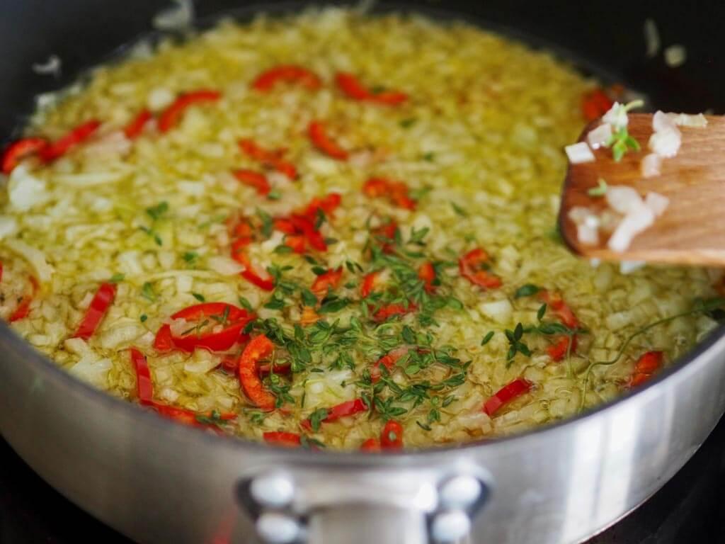 Pilkottu sipuli, valkosipuli, chili sekä timjami kuullotettavan pannulla hyvässä oliiviöljyssä.