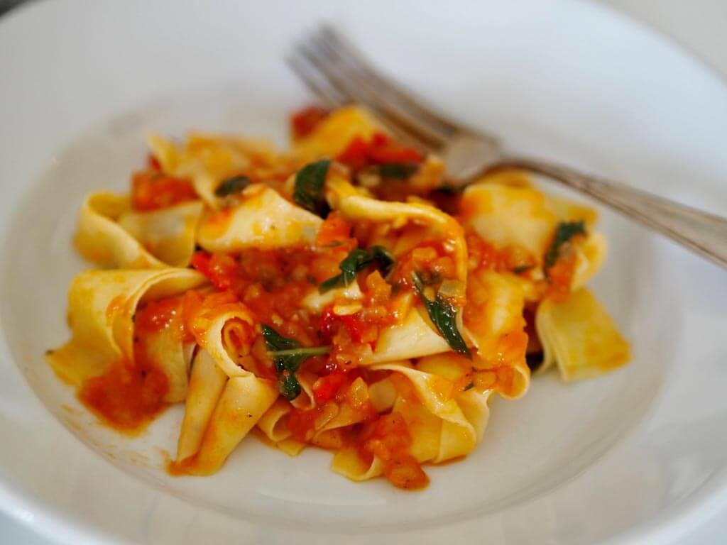 Valkoisella lautasella pappardelle pastaa sekä tomaattista soffrittoa.