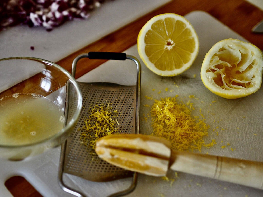 Pöydällä raastettu sitruunankuori sekä puristettu sitruunamehu.
