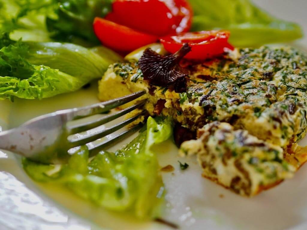 Lautasella pala sienifrittataa sekä salaattia.