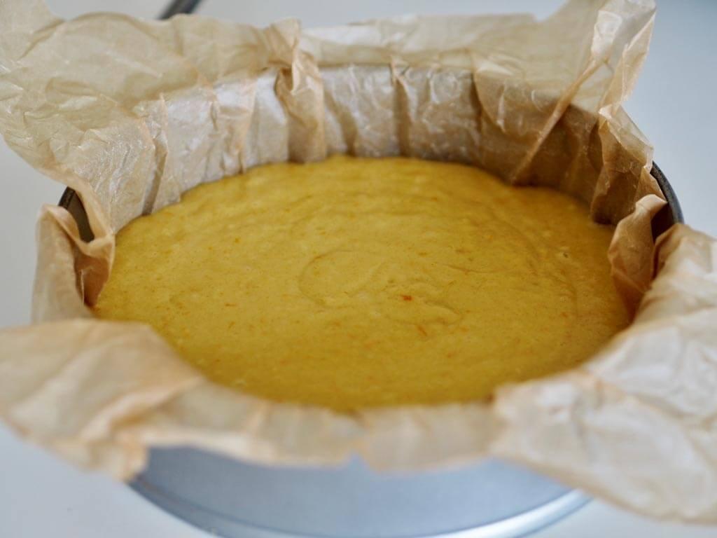 Sekoitettu appelsiinikakun taikina kaadettuna leivinpaperilla vuorattuun vuokaan.