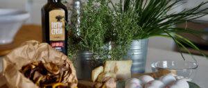 Pöydällä suppilovahveroita paperipussissa, jonka takana Terra Creta oliiviöljy.