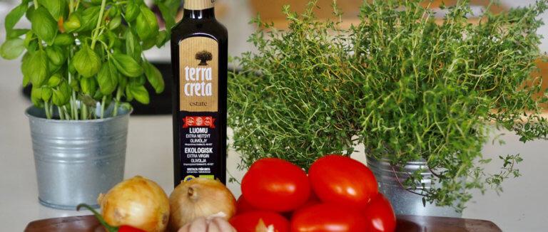 Pöydällä tomaattisen soffritton aineksia; Terra Creta oliiviöljy, tomaatit, basilika sekä sipulit.