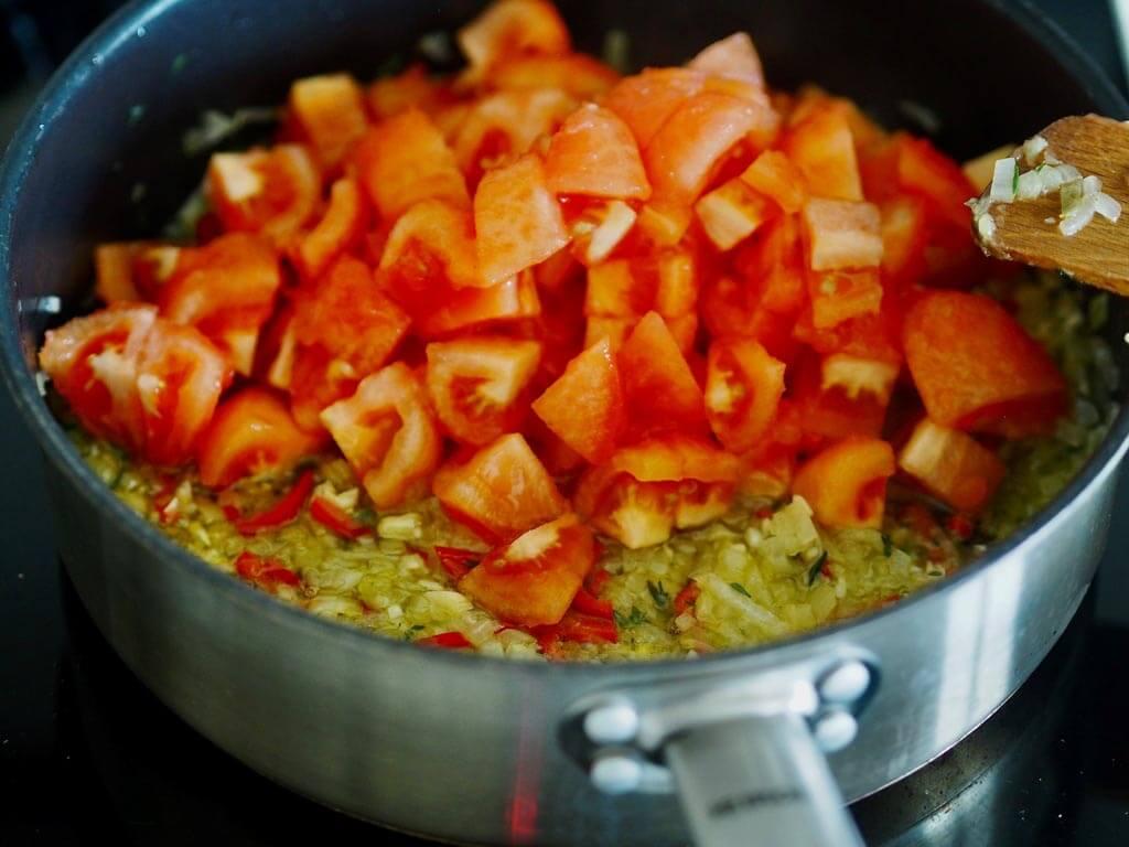 Tomaatit pannulla kuullotetun sipulin ja chilin kanssa.